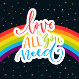 Love is all you need. Romantic quote on rainbow parade flag at dark sky with stars. Gay pride saying for stickers, t Stock Photos