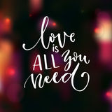 Love is all you need. Romantic saying for Valentine`s day card. Modern calligraphy. Handwritten on blurred background with lights and bokeh Stock Image
