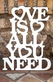 Love is all you need sing over rustic ground. Vintage decoration for weddings Royalty Free Stock Image
