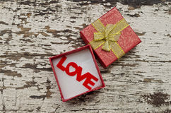 Love alphabet in gift box on grunge wood background Royalty Free Stock Images