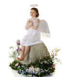 Love Angel. An elemantary angel sitting on a huge rock displaying the hand-signal for love.  She's surrounded by spring flowers.  On a white background Royalty Free Stock Photo
