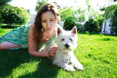 Love animals. Lovely young lady with dog, laying on grass Stock Photography