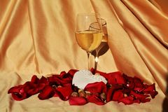 Love appreciation, symbols. A glass of white wine next to a white heart shaped object, on an elegant golden background with red petals of roses, suggesting love Royalty Free Stock Photos