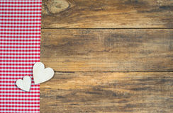 Two wooden hearts on red checkered fabric border. Love background concept, two hearts on red checkered fabric border on wood with copy space Stock Images