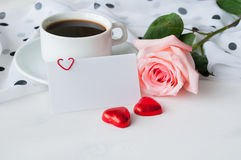 Love background - cup of coffee, rose, blank love card and two heart shaped candies Royalty Free Stock Photo