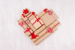 Love background - heart of gifts with red ribbons and bows on white wooden backdrop, top view stock photos