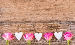 Love hearts and pink roses flowers border on rustic wood, love background for Wedding or Valentines Day. Love background with pink rose flowers and hearts border stock photo