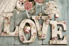 Love background with vintage style letters and roses. Lying on wooden planks stock photo