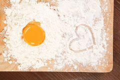 We love baking. Flour and yolk on wooden board on brown table. Baking background Stock Photography