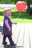 Love ballon. Baby girl holding a red heart shaped ballon stock photography