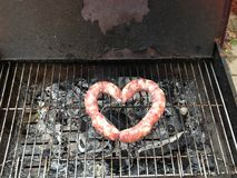 Love barbecue. Sausage , heart shape, on a grill, barbecuen Stock Images