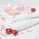 Love bath hearts candles. Bath and spa Valentine theme with white towels, pink bath stones - salt and red hearts Royalty Free Stock Images