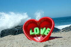 Love at the beach 1. Heart in sand with word love stock photo