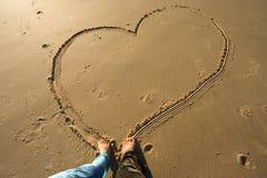 Love on the beach. Couple drawing heart on the sand Stock Photos