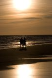 Love in a beach. Couple walking in a beach at sunset stock photography