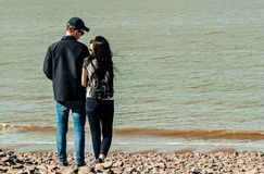 In love at the beach. A happily couple in a  beach shore holding hands and looking each other in Minehead, UK Royalty Free Stock Photo