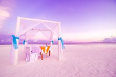 Love beach. Romantic beach dinner, white sand and white tent. Sunrise or sunset colors for couple and honeymoon background concept Stock Image