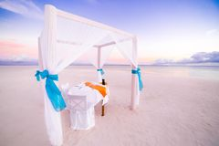 Love beach. Romantic beach dinner, white sand and white tent. Sunrise or sunset colors for couple and honeymoon background concept Royalty Free Stock Photos