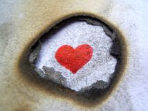 Love behind fire. Faith in love, red heart behind flame royalty free stock photo
