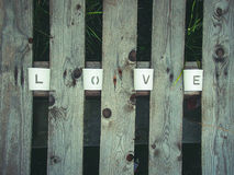 Love being spelled. The letters that creates the word love is arranged between planks Royalty Free Stock Photo