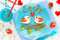 Love birds pancakes - romantic breakfast on Valentines Day. Creative idea for kids breakfast - funny pancakes shaped cute birds. With cream and strawberry royalty free stock photo