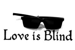 Love is blind under a pair of black shades. A photo taken on a pair of black shades sunglasses and the words `love is blind Royalty Free Stock Photography