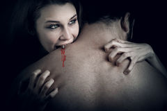 Love and blood - vampire woman biting her lover stock images