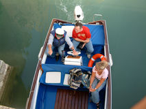 Love boat. Three people in a small boat Stock Images