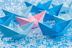 Love boat: Fleet of blue Origami paper ships on blue water like background surrounding a pink one Royalty Free Stock Image