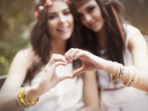 Love. Boho girls showing heart shape from hands Stock Photography
