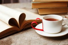 Love of books, reading. Stack of books on the wooden table. Open book with curled leaves in the shape of a heart, cup of tea. Library, education, leisure time stock image