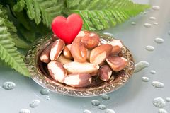 Love Brasil nuts. Brasil nuts on the plate and green leafs Stock Images