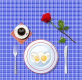 Love breakfast. Heart shaped fried eggs with red rose. Love breakfast. Heart shaped fried eggs on white plate and cup of coffee with heart on blue  chequered Royalty Free Stock Photography