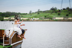 Love the bride and groom sit on the board of the ship Royalty Free Stock Photo