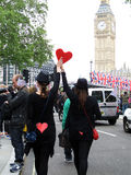 Love in Britain. Two female fans of the royal wedding between Prince William and Kate Middleton walking down the street while holding a heart. Photo taken on Stock Images