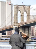 Love in Brooklyn. NEW YORK, USA - JANUARY 5, 2015: A couple enjoying the views of the Brooklyn Bridge in a winter morning royalty free stock photography