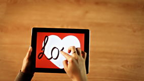 Love calligraphy. Female writing bold inside white heart on tablet stock footage