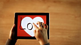 Love calligraphy. Female writing bold inside white heart on tablet. Hd stock video