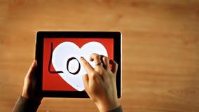 Love calligraphy. Female writing bold inside white heart on tablet stock video