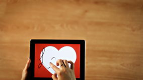 Love calligraphy. Female writing thin cursive inside white heart on tablet stock video