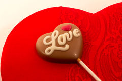 Love candy. Milk chocolate candy on a red velvet candy box Royalty Free Stock Photography