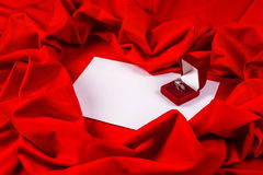 Love card with diamond ring on a red fabric Royalty Free Stock Photography