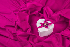 Love card with heart on a purple fabric. Love card. white heart with a purple ribbon on a purple fabric Stock Photography