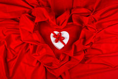 Love card with heart on a red fabric. Love card. white heart with a red ribbon on a red fabric Stock Photo