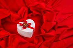 Love card with heart on a red fabric. Love card. white heart with a red ribbon on a red fabric Stock Image