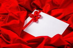 Love card with heart and ribbon on a red fabric Royalty Free Stock Images