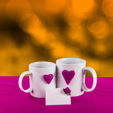 Love card with heart on a tea cup. Love card with blur background. purple heart on a white tea cup on a gold background Stock Photography