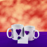 Love card with heart on a tea cup. Love card with red blur background. blue heart on a white tea cup on a blue fabric Royalty Free Stock Photo