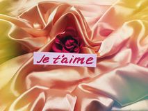 Love card with phrase i love you written in french. Beautiful romantic background with love note and rose on drapery shiny silk Royalty Free Stock Photo
