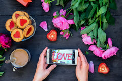 Love and care concept. Female hands holding smartphone surrounded with peonies, cookies and mug with coffee, candles on the black. Wooden background. Romantic Stock Image